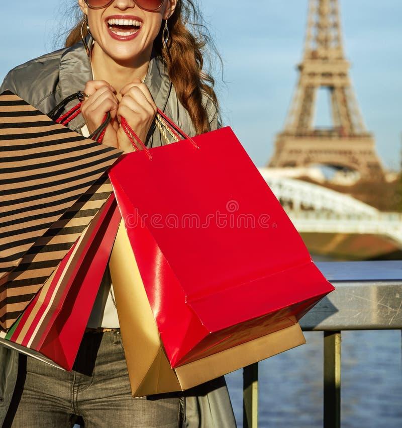 Den gladlynta eleganta kvinnan med shoppingpåsar near Eiffeltorn fotografering för bildbyråer