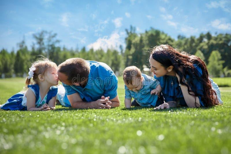 Den gladlynta familjen i en parkera, föräldrar och deras två barn ligger på gräset Skott med signalljuset fotografering för bildbyråer