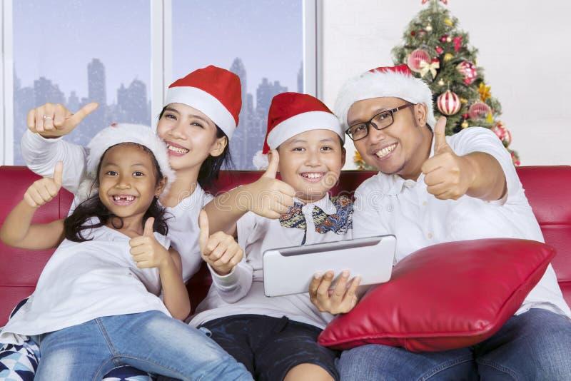 Den gladlynta familjen med jultomtenhattshow tummar upp royaltyfri bild