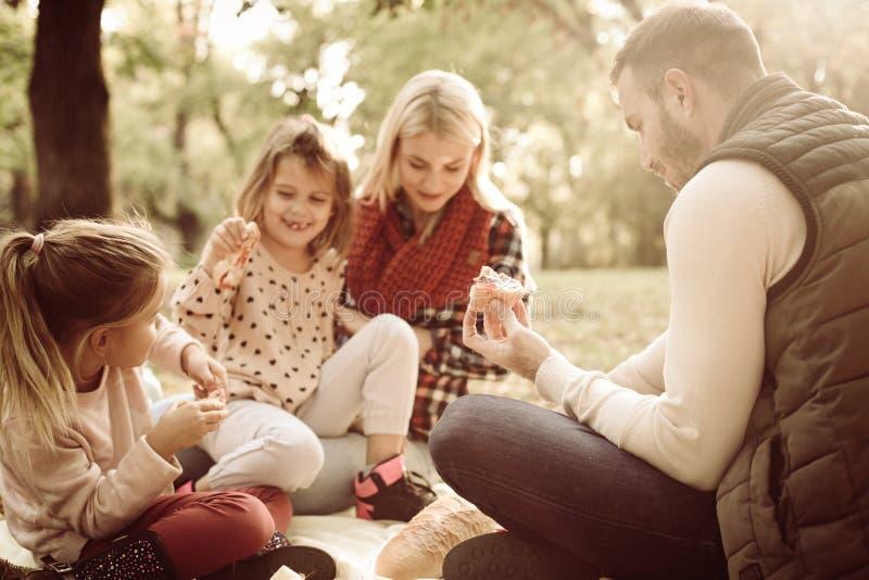 Den gladlynta familjen parkerar in att ha picknicken arkivfoto