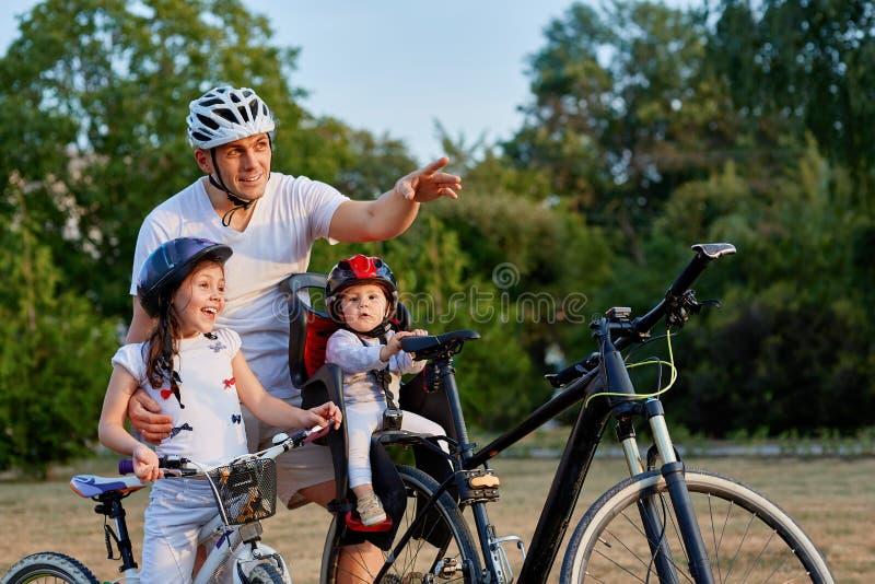 Den gladlynta familjen som in cyklar, parkerar royaltyfria bilder
