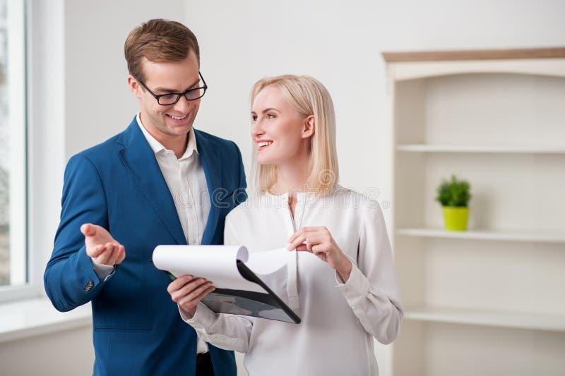 Den gladlynta fastighetsmäklaren talar med en kund royaltyfri bild