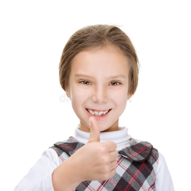 Den gladlynta flickan lyfter tummen uppåt arkivbilder