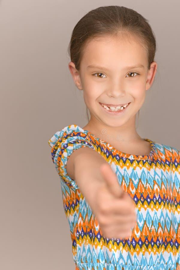 Den gladlynta flickan lyfter tummen uppåt arkivbild