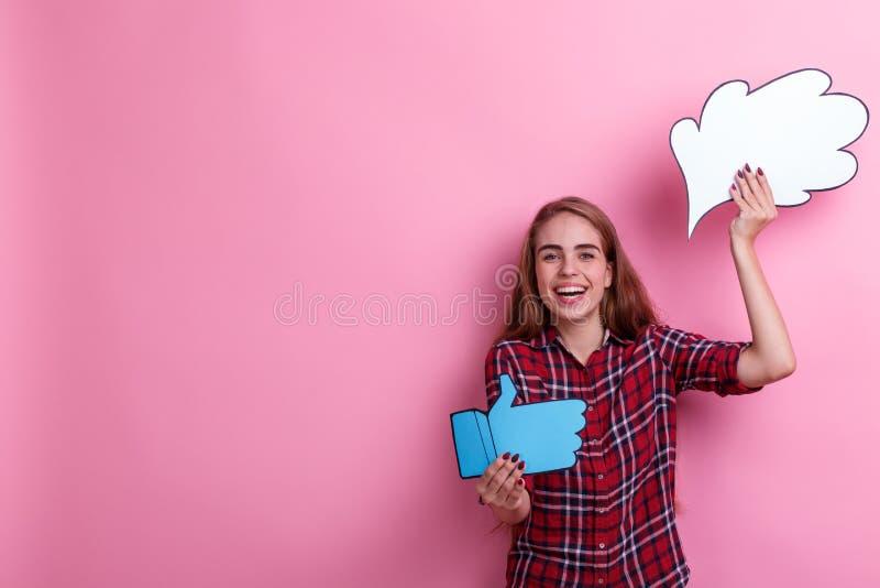 Den gladlynta flickan som rymmer en pappers- bild av tanke eller idén, och ett tecken av återkoppling tummar upp och att skratta royaltyfria foton