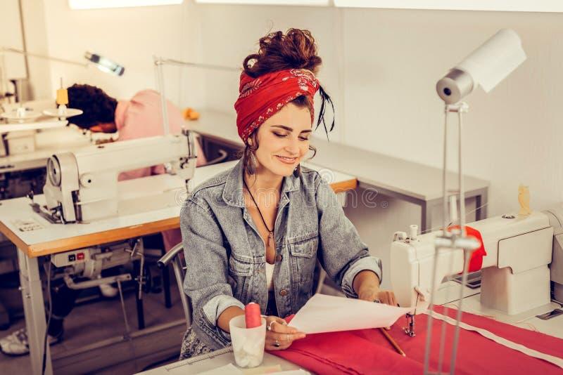 Den gladlynta formgivaren som ser hennes, skissar nära symaskinen royaltyfri foto