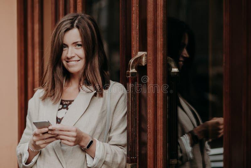 Den gladlynta glade kvinnlign med mörkt rakt hår, bruk ilar telefonen, iklädda eleganta kläder, blickar positivt på kameran, tyck arkivfoton