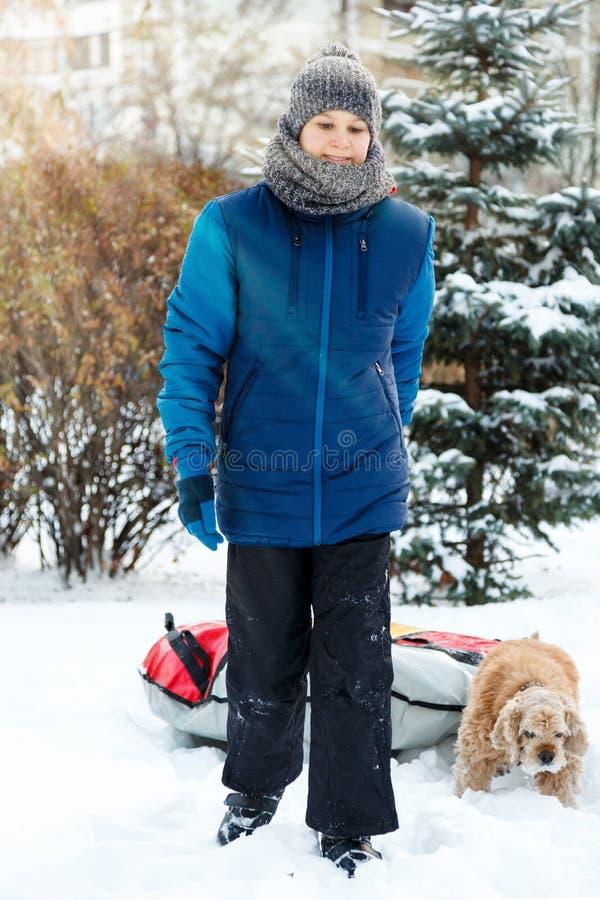 Den gladlynta gulliga unga pojken i blått omslag rymmer röret på snö, har gyckel, leenden Tonåringen på sledding i vinter parkera royaltyfri bild