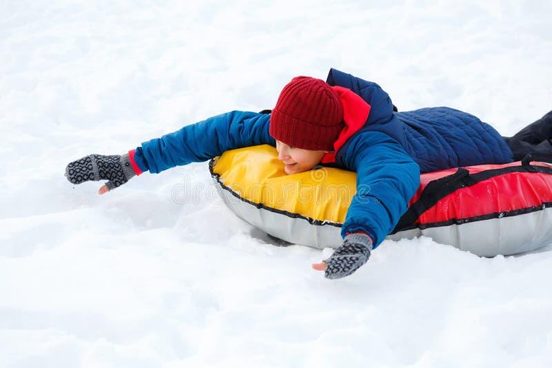 Den gladlynta gulliga unga pojken i röd halsduk för orange hatt och blått omslag rymmer röret på snö, har gyckel, leenden Tonårin fotografering för bildbyråer