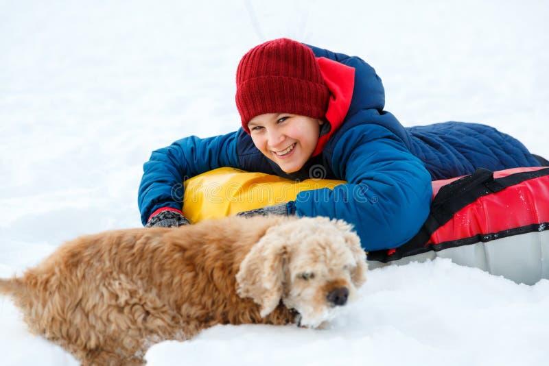 Den gladlynta gulliga unga pojken i röd halsduk för orange hatt och blått omslag rymmer röret på snö, har gyckel, leenden Tonårin arkivbild
