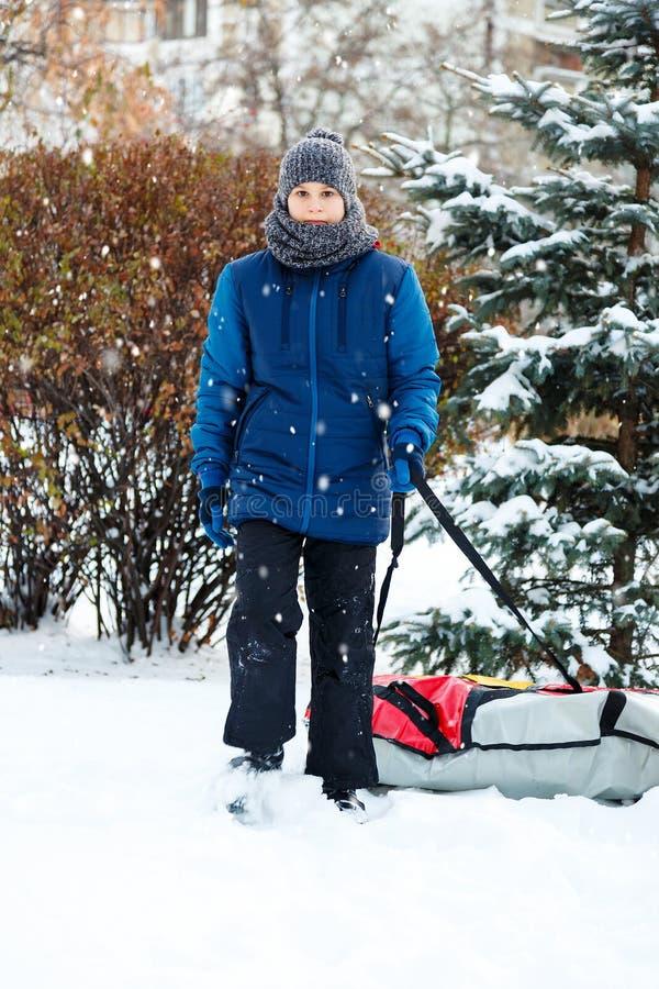 Den gladlynta gulliga unga pojken i röd halsduk för orange hatt och blått omslag rymmer röret på snö, har gyckel, leenden Tonårin arkivbilder
