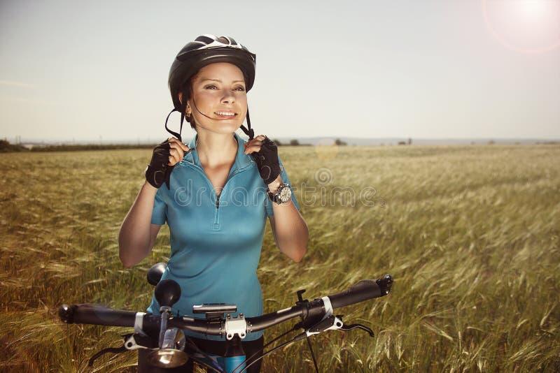 Den gladlynta härliga unga kvinnan med en cykel på ett fält fäster honom royaltyfria bilder