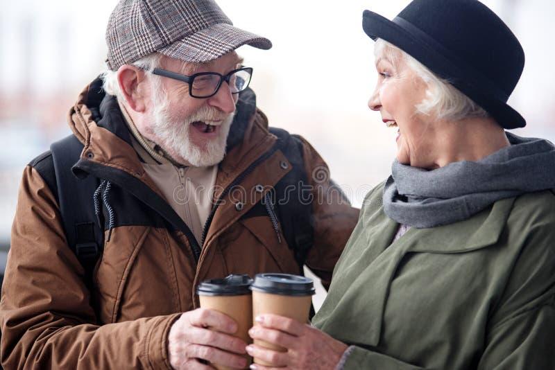 Den gladlynta höga mannen och kvinnan rymmer kaffe med leende royaltyfria bilder