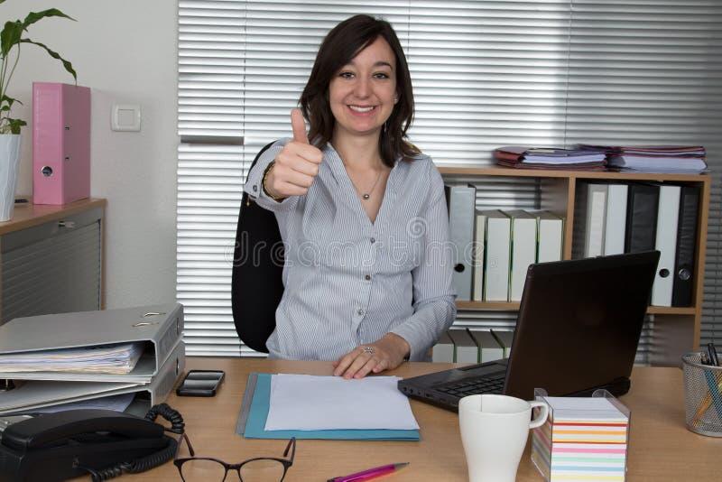 Den gladlynta kontor-arbetare visningen tummar upp framme av bärbara datorn arkivfoto