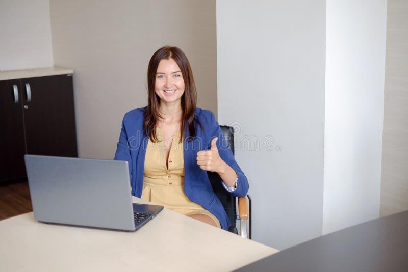 Den gladlynta kontor-arbetare visningen tummar upp framme av bärbara datorn royaltyfria foton