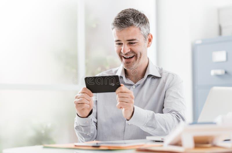 Den gladlynta kontorsarbetaren som förbinder med hans smartphone, håller ögonen på han en video och social nätverkande royaltyfri foto