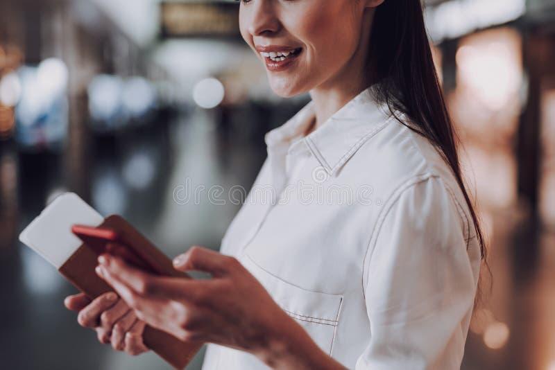 Den gladlynta kvinnan använder smartphonen i flygplats arkivfoton