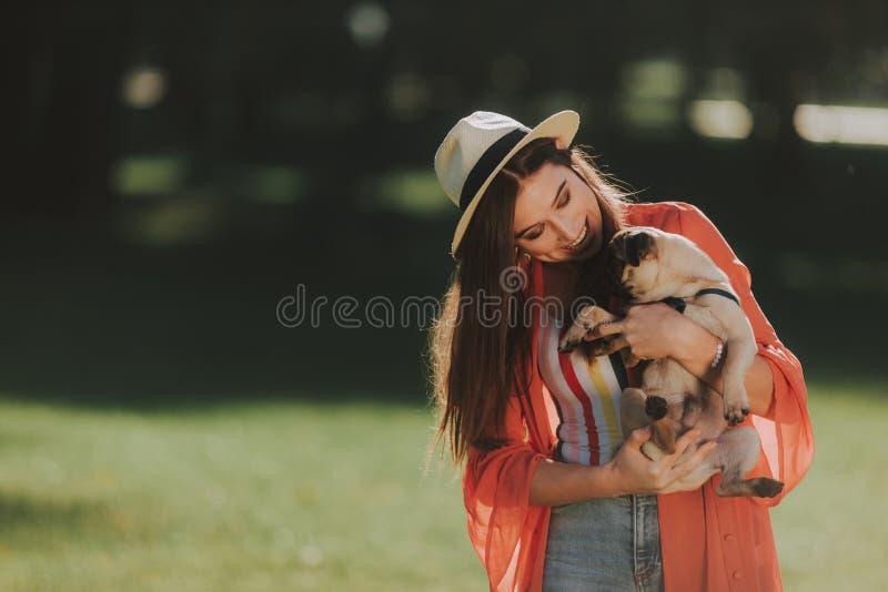 Den gladlynta kvinnan kramar hennes lilla hund royaltyfri foto