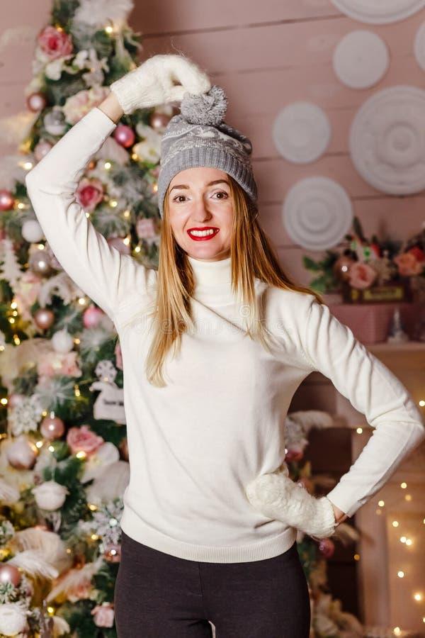 Den gladlynta kvinnan med röda kanter i en stucken hatt står på en julgranbakgrund, juldekor royaltyfria bilder