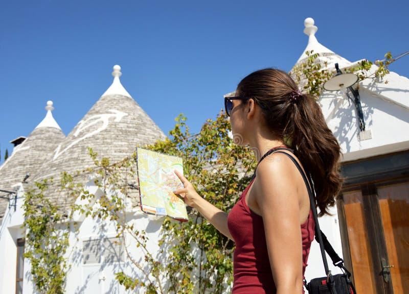 Den gladlynta kvinnan med solglasögon och långt hår som söker riktning på lägeöversikt, medan resa utomlands, den lyckliga kvinnl arkivfoto