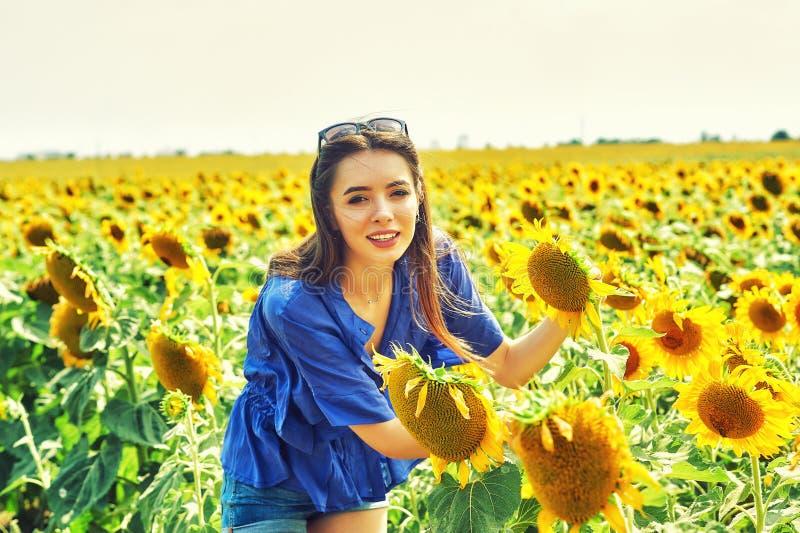 Den gladlynta kvinnan på en sommar går i fältet med solrosor royaltyfri fotografi