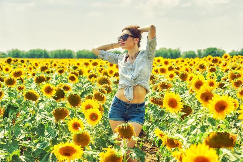 Den gladlynta kvinnan på en sommar går i fältet med solrosor arkivbilder