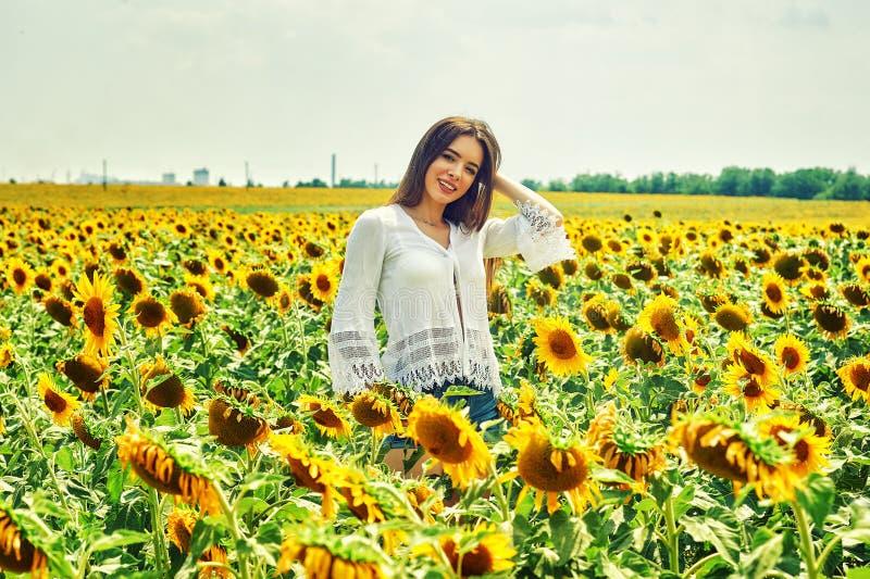 Den gladlynta kvinnan på en sommar går i fältet med solrosor arkivbild