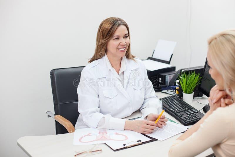 Den gladlynta kvinnliga doktorn råder hennes patient royaltyfri foto