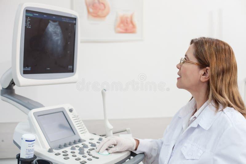 Den gladlynta kvinnliga gynekologen undersöker hennes patient arkivbild