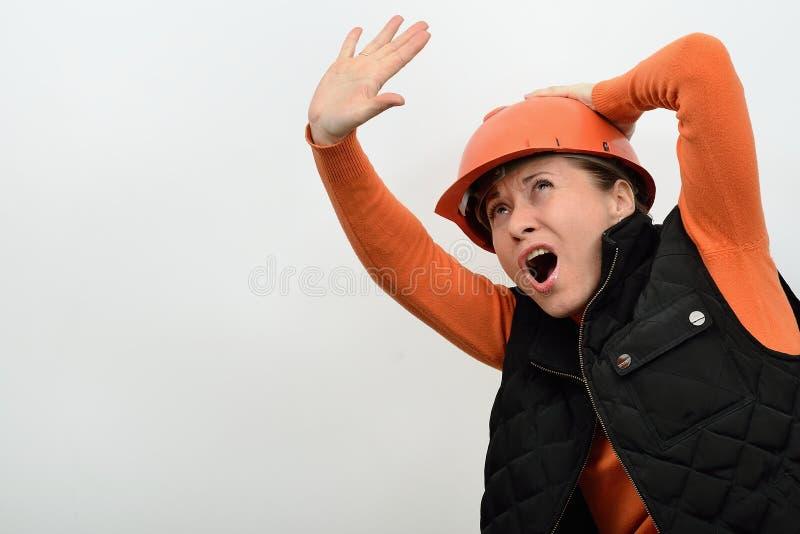 Den gladlynta le kvinnabyggnadsarbetaren med elektrisk skruvmejsel och hjälpmedel i händerna av en grinighet såg royaltyfri bild