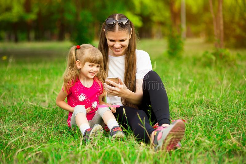 Den gladlynta le lyckliga modern och hennes lilla dotter sitter p? gr?nt gr?s i sommar parkerar royaltyfria foton