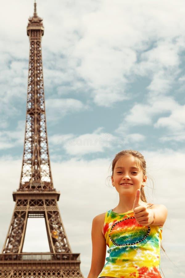 Den gladlynta le turist- visningen för flicka tummar upp framgångtecken framme av Eiffeltorn, Paris arkivbilder