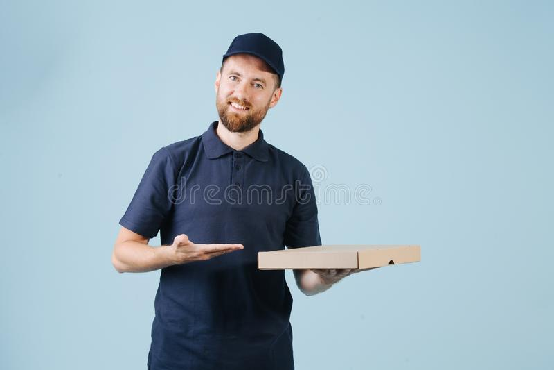 Den gladlynta leveransmannen i likformig rymmer papppizzaasken arkivfoton