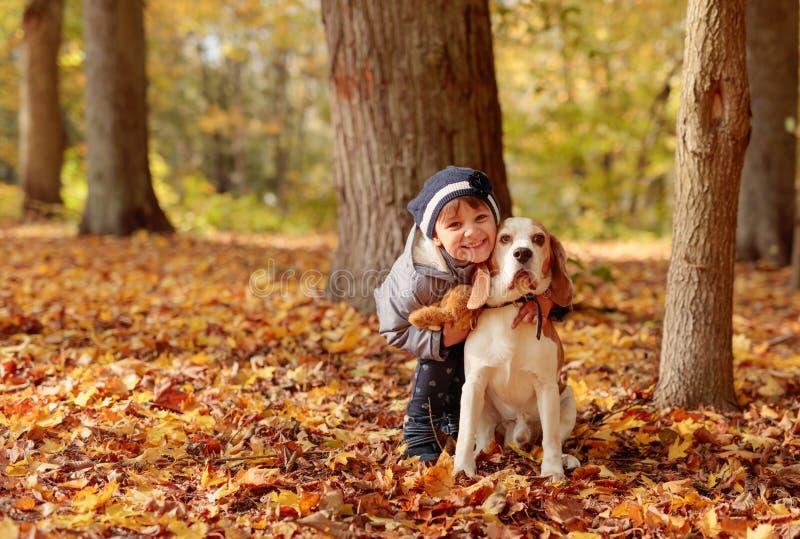 Den gladlynta lilla flickan kramar hennes hund royaltyfri foto