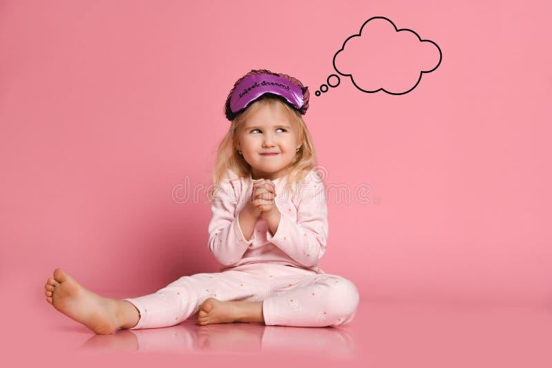 Den gladlynta lilla gulliga flickan i pyjamas sitter på golvet på en rosa bakgrund i en sömnmaskering i morgonen och drömmarna om arkivfoton