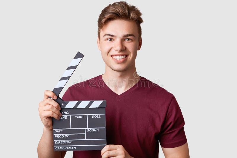 Den gladlynta mannen med brett leende, bär den tillfälliga t-skjortan, rymmer clapperboarden som deltas i den nya filmen för skap royaltyfri foto