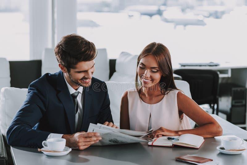 Den gladlynta mannen och kvinnan läser tidningen i kafé royaltyfri fotografi