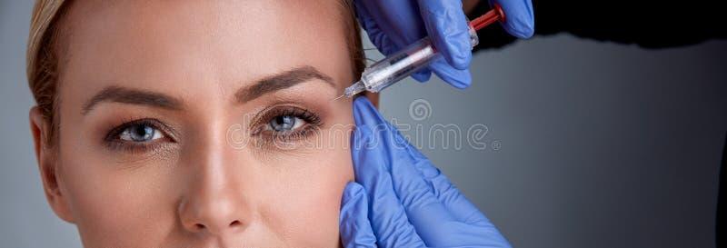 Den gladlynta mellersta ålderkvinnan får botoxtillvägagångssätt royaltyfri fotografi