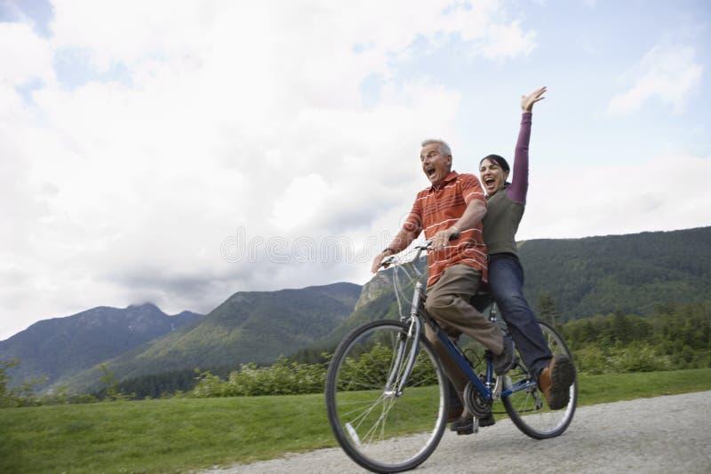 Den gladlynta mitt åldrades par som cyklar på landsvägen arkivfoton