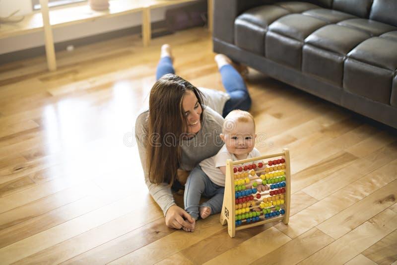 Den gladlynta modern som spelar med hans, behandla som ett barn flickan på golv på vardagsrum arkivfoto