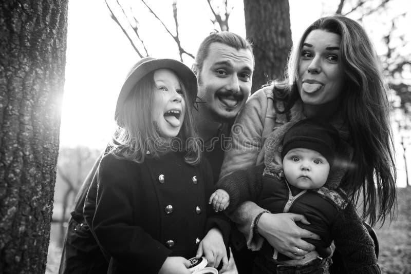 Den gladlynta och lyckliga familjen i höst parkerar royaltyfri bild