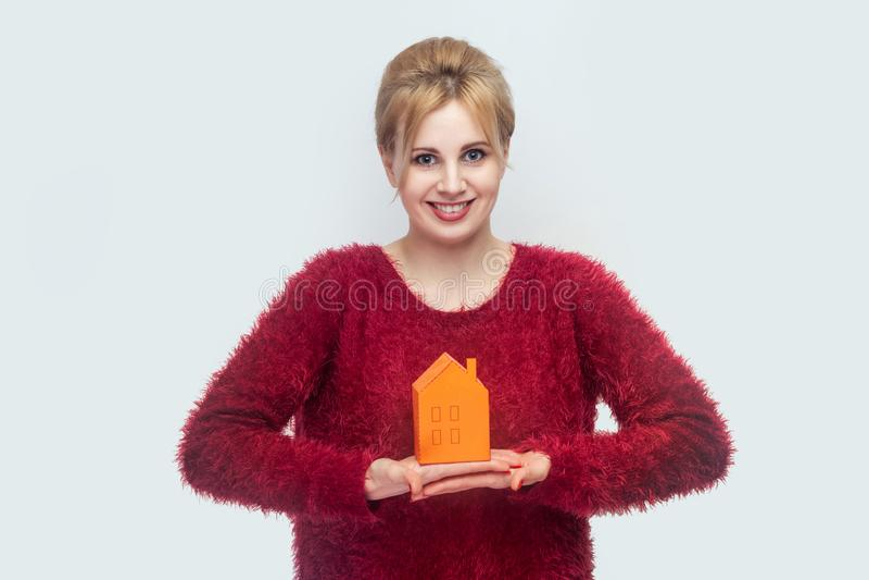 Den gladlynta positiva glade optimistiska unga kvinnan i rött blusanseende och har dröm och att rymma det pappers- lilla huset so arkivbilder