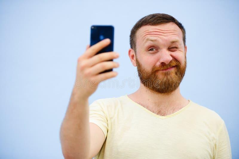 Den gladlynta skäggiga mannen blinkar på telefonen som är passande för annonsering, på en blå bakgrund arkivbilder