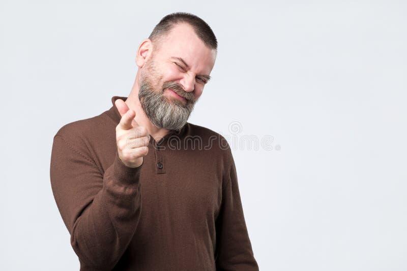 Den gladlynta sk?ggiga mannen i tillf?llig kl?der indikerar lyckligt p? dig arkivfoton