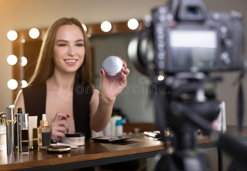 Den gladlynta skönhetbloggeren visar nya produkten royaltyfri bild