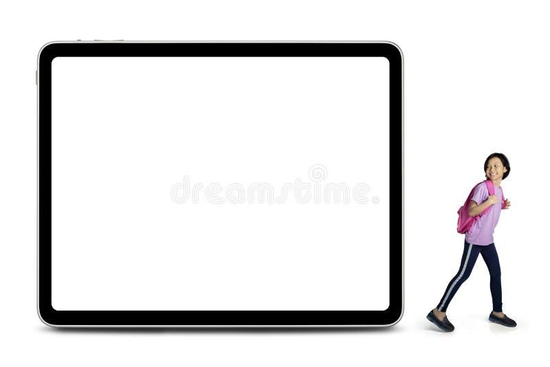 Den gladlynta skolflickan ser en tom whiteboard royaltyfria bilder