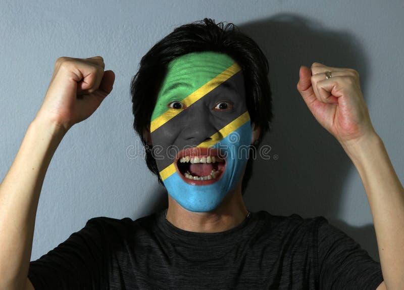 Den gladlynta ståenden av en man med flaggan av Tanzania målade på hans framsida på grå bakgrund Begreppet av sporten eller natio fotografering för bildbyråer