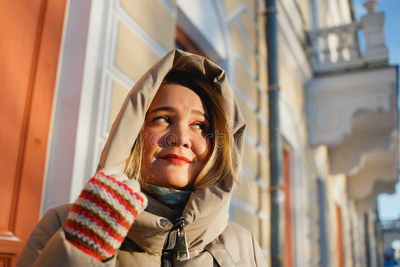 Den gladlynta stilfulla flickan som tycker om vinter, går på en frostig solig dag Henne som rymmer hennes huv vid tumvanten Begre royaltyfri bild