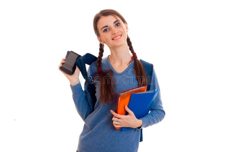 Den gladlynta tonåriga flickan ser in i kameran och rymmer mappar med anteckningsböcker royaltyfri foto
