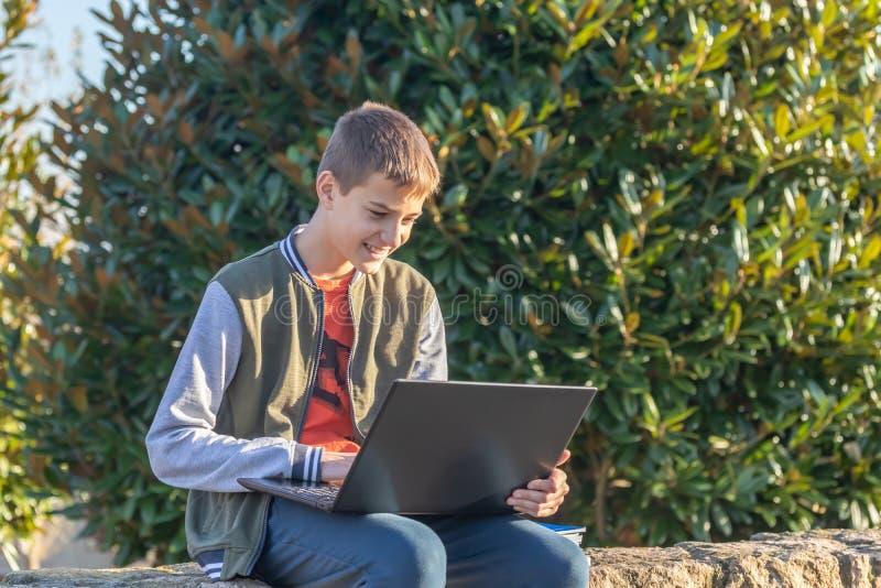 Den gladlynta tonåringpojken med bärbara datorn och läroböcker som gör läxa och förbereder sig för en examen i, parkerar royaltyfria bilder